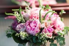 与白玫瑰、绯红色牡丹和绿色的土气婚礼花束在一个木地板上 户内 图库摄影