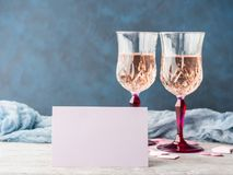 与白纸卡片的两块桃红色香槟玻璃 免版税库存照片