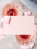 与白纸卡片的两块桃红色香槟玻璃 库存照片