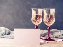 与白纸卡片的两块桃红色香槟玻璃 图库摄影