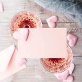 与白纸卡片的两块桃红色香槟玻璃 免版税库存图片
