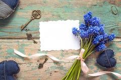 与白纸卡片,蓝色花花束,牛仔布的背景 库存图片