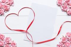 与白纸板料和桃红色玫瑰的红色丝带心脏标志 免版税库存图片