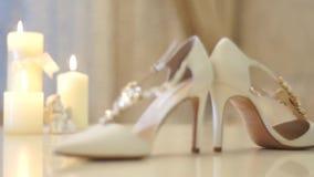 与白色丝带和婚礼鞋子的美好的蜡烛 股票录像