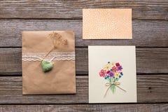 与白色丝带的信封和与花的两张明信片 免版税库存图片