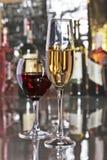 与白色两块的玻璃和红葡萄酒葡萄的庆祝构成在镜子桌上 库存照片