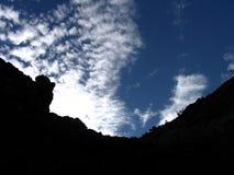 与白色云彩和山剪影的蓝天 图库摄影