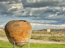 与白色云彩的剧烈的蓝天在一个古老罐的废墟-在Histria的amphorae,黑海岸的  Histria是 免版税库存照片