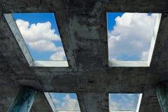 与白色云彩的蓝天能通过在一个混凝土建筑的窗口被看见 信念、自由和希望的概念 免版税库存照片