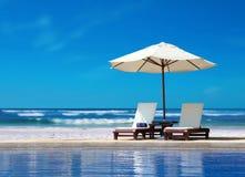 与白色伞的两把椅子在海滩 免版税库存照片