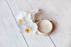 与白色兰花的面霜在木桌上 免版税库存照片