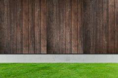 与白色具体和木篱芭的绿草 免版税图库摄影
