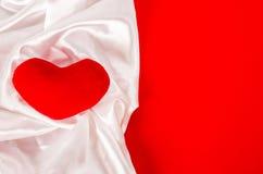 与白色典雅的织品的红色心脏在红色背景 图库摄影