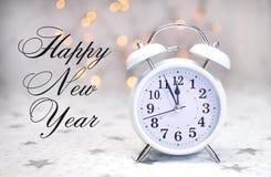 与白色减速火箭的时钟的新年快乐消息有样品文本的 库存图片