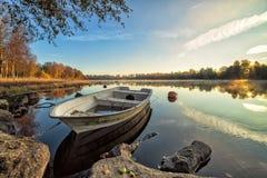 与白色划艇的田园诗秋天湖风景 免版税图库摄影