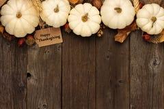 与白色南瓜顶面边界的愉快的感恩礼物标记在木头的 免版税库存图片