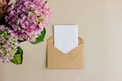 与白色卡片的牛皮纸信封在轻的背景 免版税图库摄影