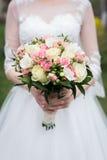 与白色和桃红色玫瑰的新娘花束 白色婚礼礼服的新娘拿着与白色和桃红色ro的婚礼花束 免版税库存图片