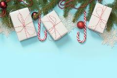 与白色和红色装饰,礼物,棒棒糖,在蓝色背景的雪花的圣诞节创造性的边界 平的位置 顶视图 复制温泉 免版税库存照片
