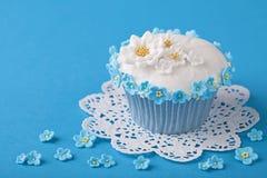 与白色和蓝色花的杯形蛋糕 库存图片