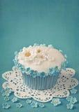 与白色和蓝色花的杯形蛋糕 库存照片