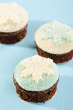 与白色和蓝色雪剥落的圣诞节杯形蛋糕 库存照片