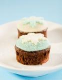 与白色和蓝色雪剥落装饰的圣诞节杯形蛋糕。在 库存图片