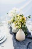 与白色和绿色花的美好的桌设置 免版税图库摄影