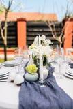 与白色和绿色花的美好的桌设置 免版税库存照片