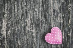 与白色圆点样式的桃红色减速火箭的心脏在木backgrou 库存照片