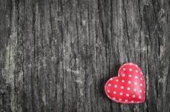与白色圆点样式的红色减速火箭的心脏在木backgroun 免版税库存图片