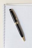 与白色垫或笔记薄的黑笔 库存图片