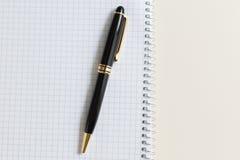 与白色垫或笔记薄的黑笔 免版税库存图片