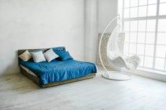 与白色墙壁和现代床的Minimalistic内部 大窗口公寓 免版税图库摄影
