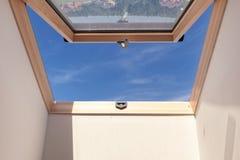 与白色墙壁的被打开的屋顶窗口屋顶窗反对蓝天 免版税图库摄影