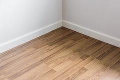 与白色墙壁,室` s角落的被碾压的木地板 免版税库存照片