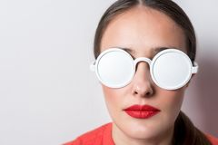 与白色太阳镜的美丽的年轻女人画象在明亮的背景 免版税图库摄影