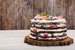 与白色奶油和新鲜水果的巧克力蛋糕 免版税库存图片