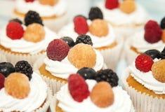 与白色奶油和莓果的杯形蛋糕 库存照片