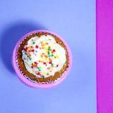 与白色奶油的杯形蛋糕在桃红色和蓝色背景, 库存图片
