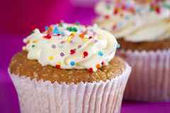 与白色奶油的杯形蛋糕在桃红色背景, 库存图片