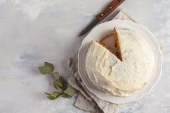 与白色奶油的红萝卜自创蛋糕在白色板材,灰色backg 库存照片