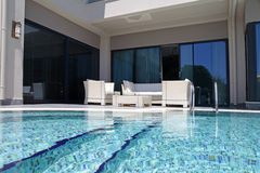 与白色室外家具的游泳池在现代豪华reso 免版税库存照片