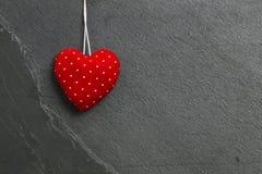与白色小点的红色爱垂悬在灰色板岩的华伦泰的心脏 库存照片