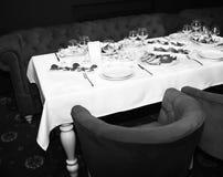与白色布料的表在红色扶手椅子和沙发附近 餐馆桌服务与快餐和沙拉 免版税图库摄影