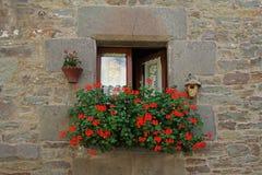 与白色帷幕、鸟舍、垂悬的罐和装饰的大竺葵的窗口在Rupit开花 库存图片