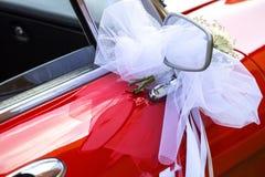 与白色弓的一点花花束在一辆红色汽车 库存图片
