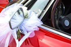 与白色弓的一点花花束在一辆红色汽车 免版税库存照片