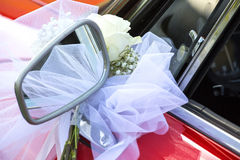 与白色弓的一点花花束在一辆红色汽车 库存照片