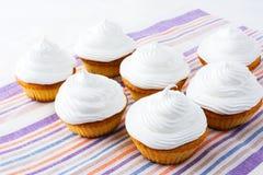 与白色打好的奶油的杯形蛋糕 库存图片